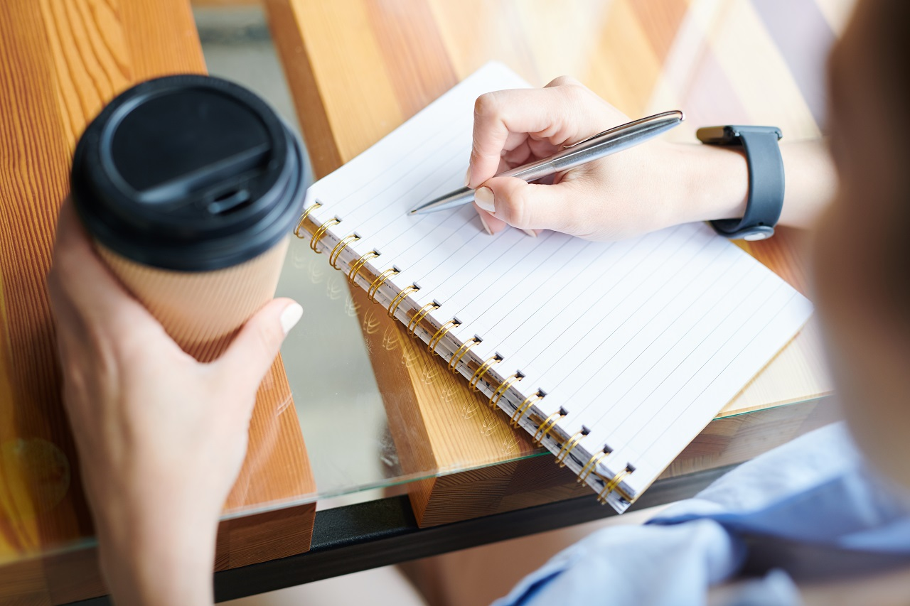 girl writing on a notebook while holding a cup of coffee perched on top of a table made of wood and glass