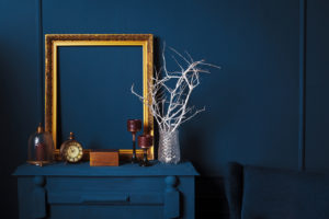 Blue wall with blue furniture and a gold picture frame