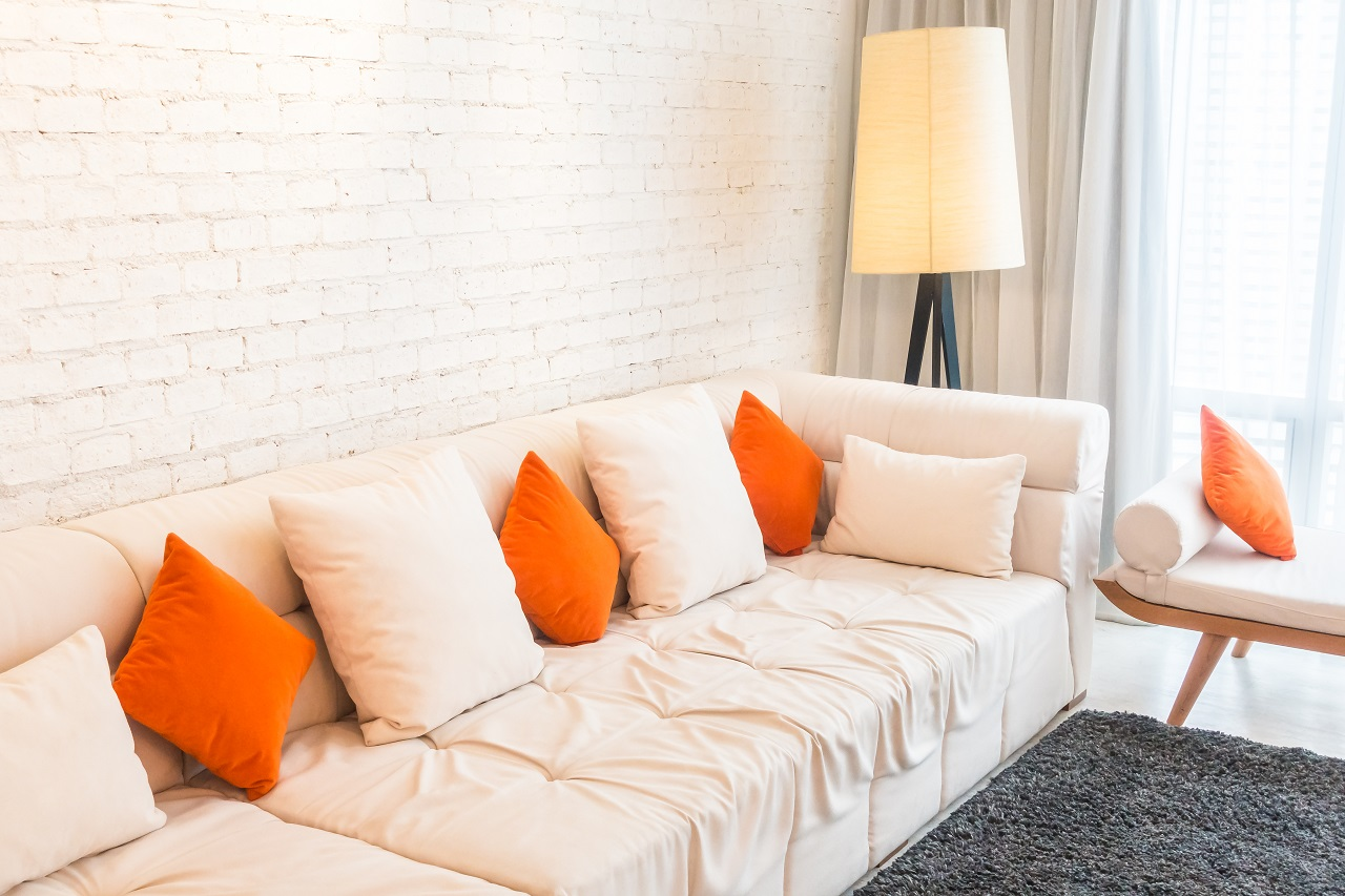 Orange pillows on a white sofa